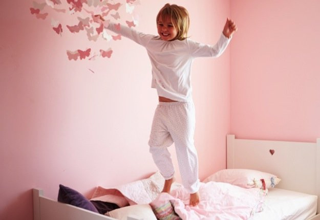 little girl in pyjamas jumping on her bed