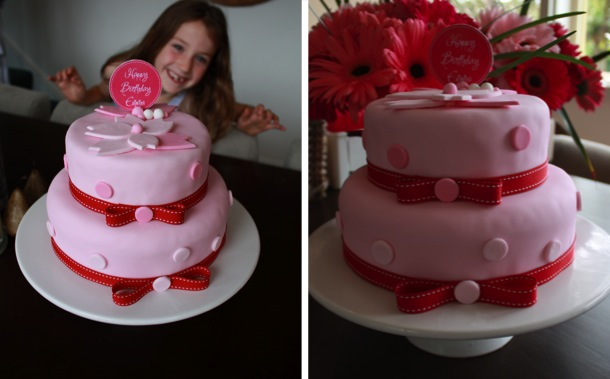 Pink and red layered cake with polka dots, red ribbon and a flower on top