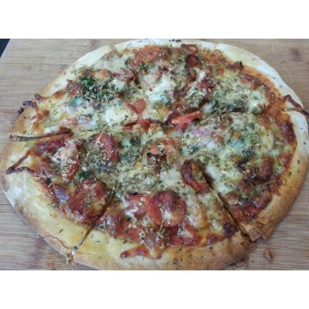 Home made wood fired pizza seasoned with italian spaghetti herbs