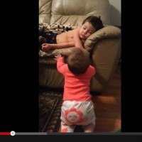 Too cute! Watch this little sister try to wake up her big brother!