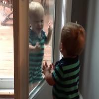 Video: Twin boys find door window hilarious