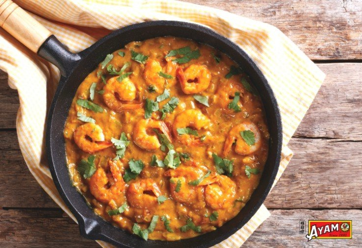 skillet filled with delicious ayam prawn red curry and topped with chopped coriander