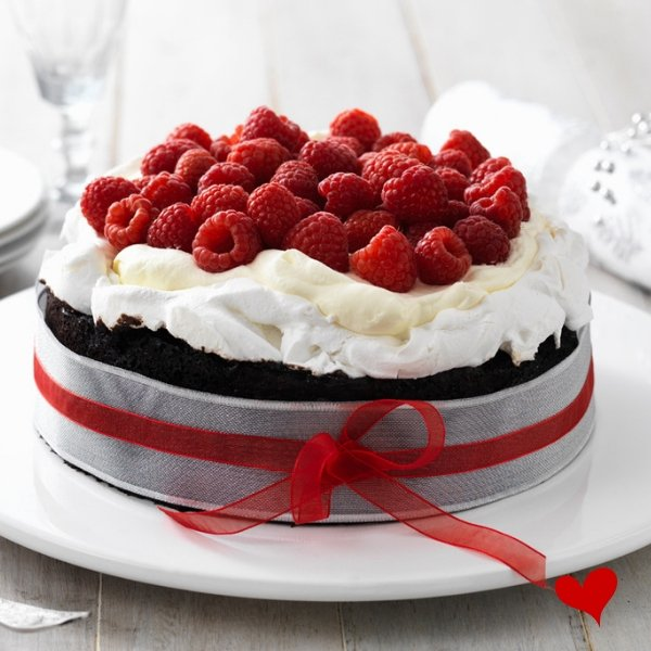 rich round chocolate cake wrapped in silver foil with red ribbon topped with pavlova topping and raspberries