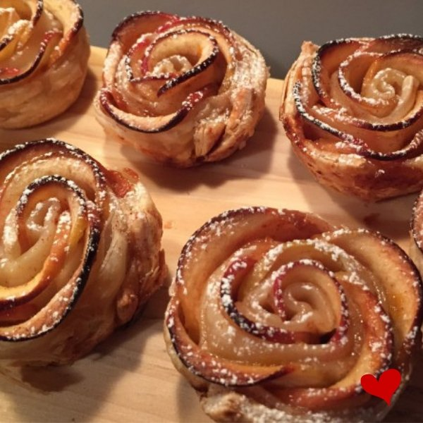 Rose tartlets made from long strips of apple peel, baked until golden brown and then dusted with icing sugar