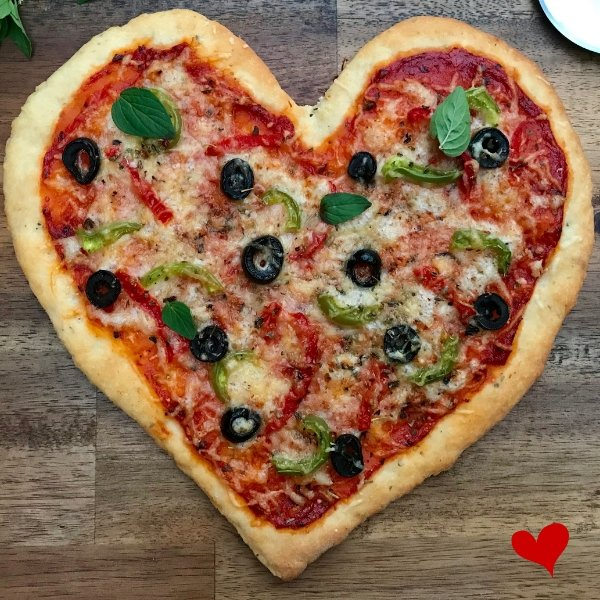 Heart shaped pizza topped with tomato paste black olives fresh herbs and cheese