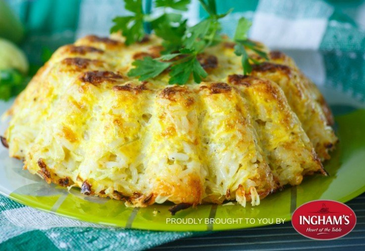 Chicken and Cheese Rice Pie. A golden brown rice dish that has been oven baked in a shaped baking tray and then inverted to serve. Topped with fresh green parsley