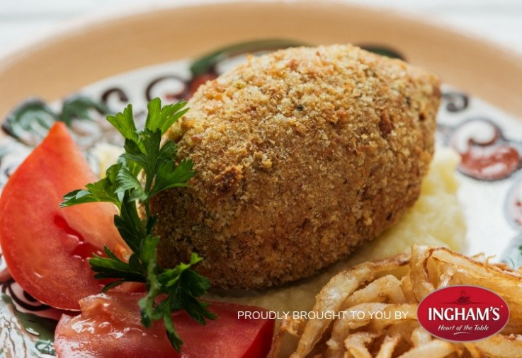 Golden brown crumbed Turkey and Tahini Kofta sitting on a plate with fresh green herbs, slices of tomato and a swipe of hummous