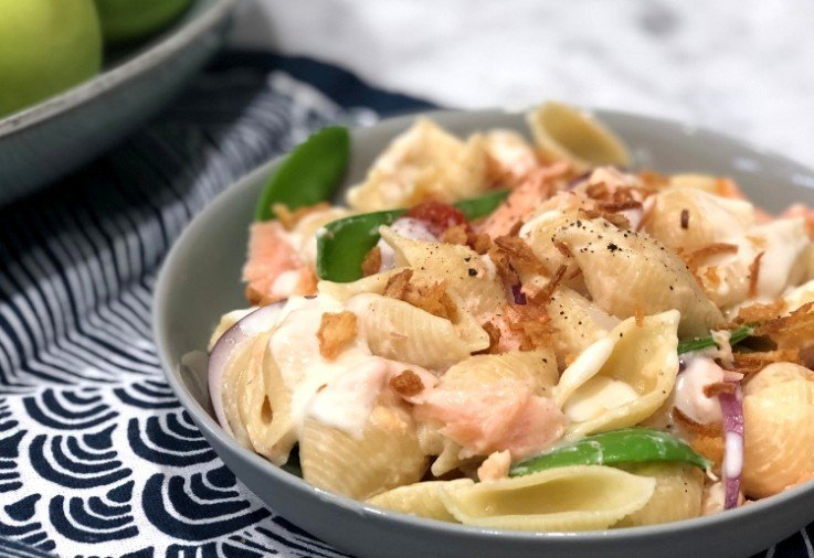 Grey bowl of pasta shells cooked with Hot Smoked Salmon, Green Snow Peas, Cherry Tomatoes, Red Onion, a creamy sauce and crispy onion sprinkles