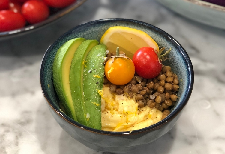 Small blue and brown pottery style bowl containing a serve of scrambled eggs, some brown lentils, 1/4 avocado sliced, a wedge of lemon and 2 cherry tomatoes