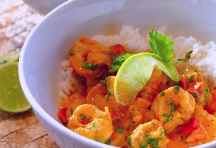 white bowl filled with white rice and a delicious thai prawn red curry topped with a wedge of lime and fresh green herbs