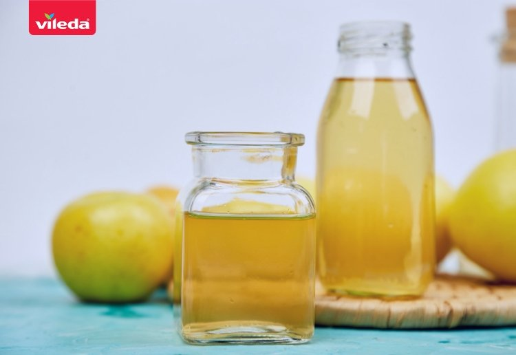 apple cider vinegar in two small bottles with a yellow apple in the background on a blue tabletop
