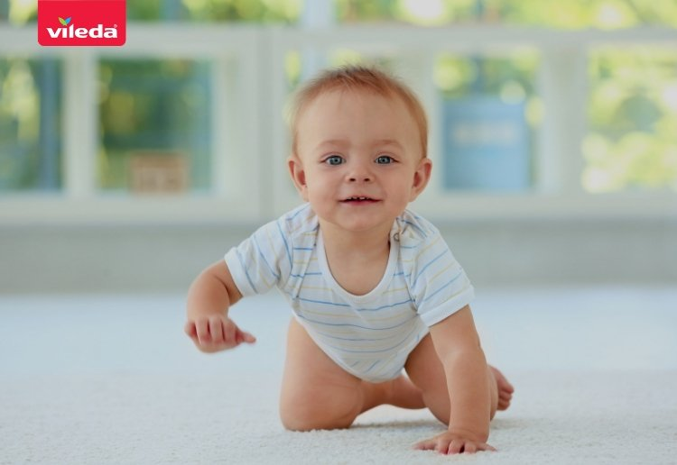 cute baby in short babygro suit crawling towards the camera with windows and leafy view in background