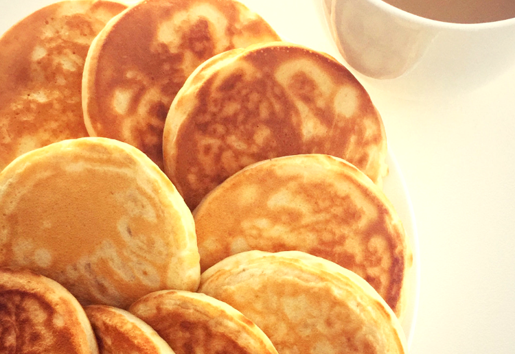 A batch of mini pancakes that are cooked to perfection