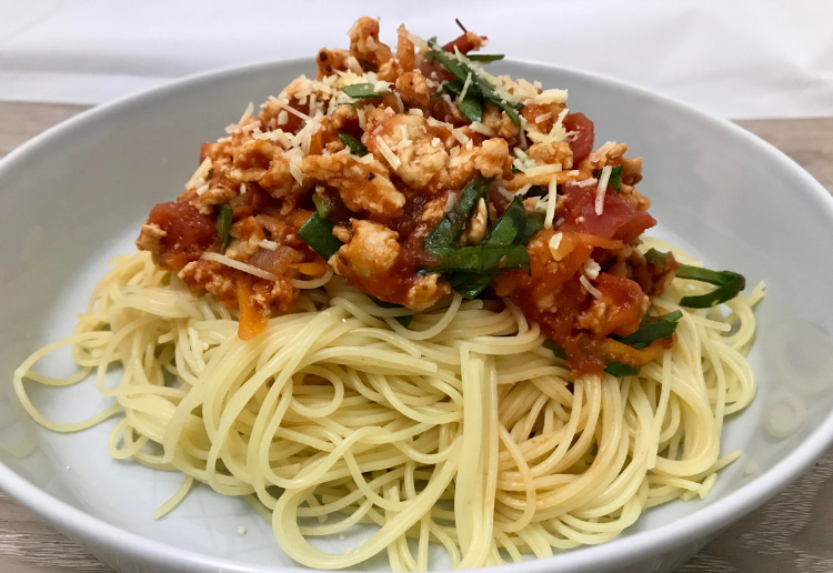 White bowl filled with thin spaghetti and topped with a rich Chicken Cacciatore tomato based sauce and garnished with fresh green herbs