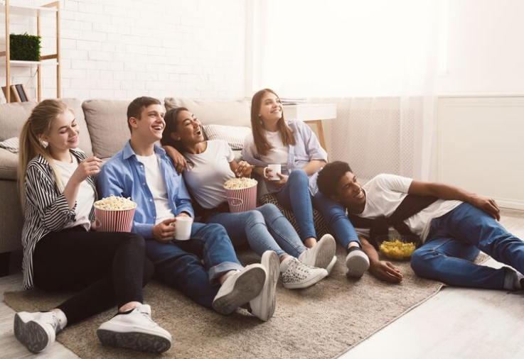HANGING OUT - Group of young adults eating popcorn and watching a movie