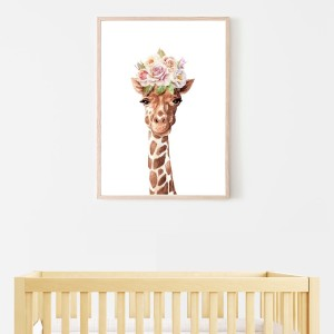 picture of a cute giraffee framed on a wall above a wooden cot