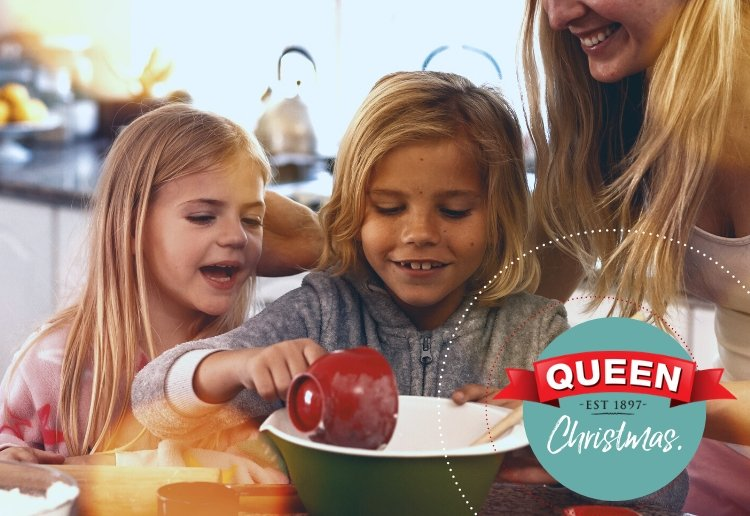 Christmas Baking with Mother and her children gathered around a bowl emptying ingredients in