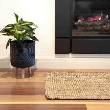 Jute runner placed in hallway with green plant and fireplace