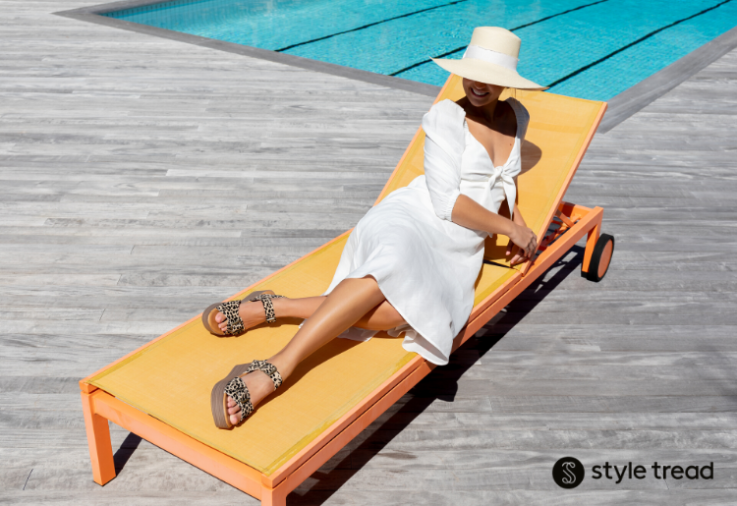 Woman wearing Leeds Natural Leopard shoes from Styletread, reclining on a sunlounger in the sun