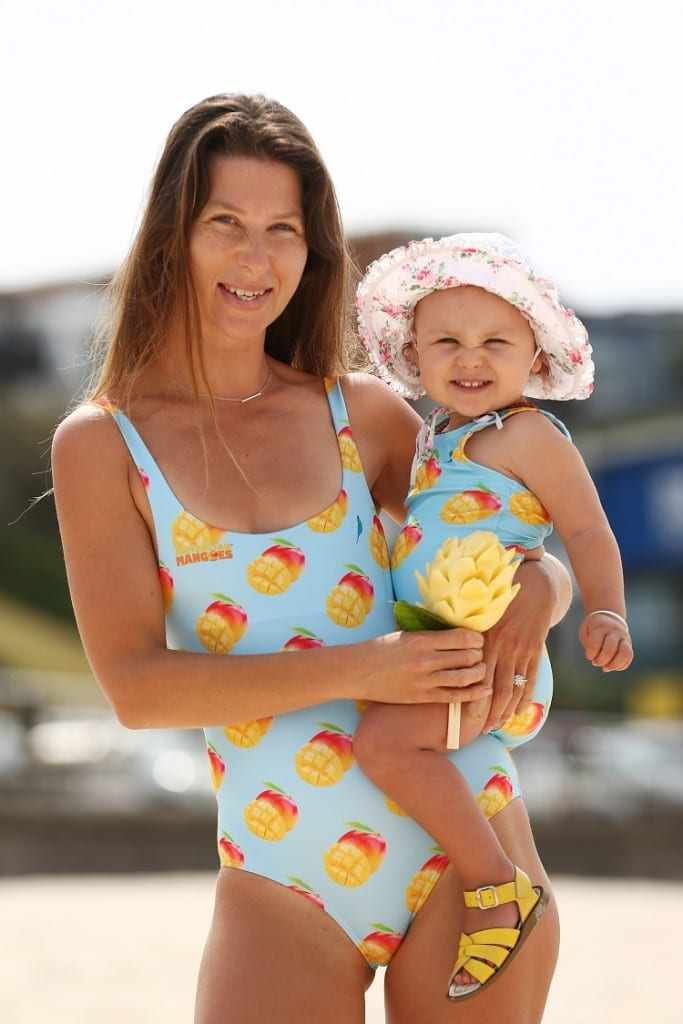 A mum and baby in matching swimwear on the beach