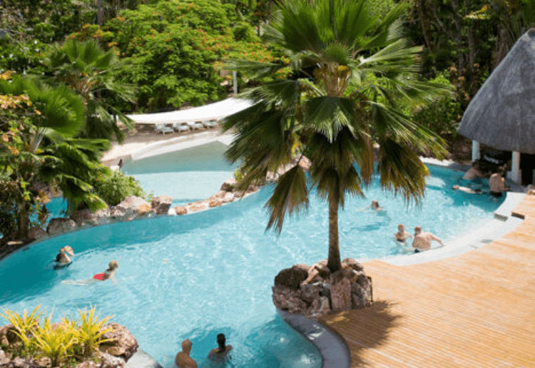 A sunny day reveals verdant palms and guests in the pool at Malolo resort in Fiji.