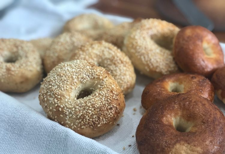 a bagel selection on a tray with sesame seed bagel and cinnamon bagel