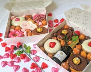A box of sweet treats - bottle of sparkling wine and lots of love heart chocolates