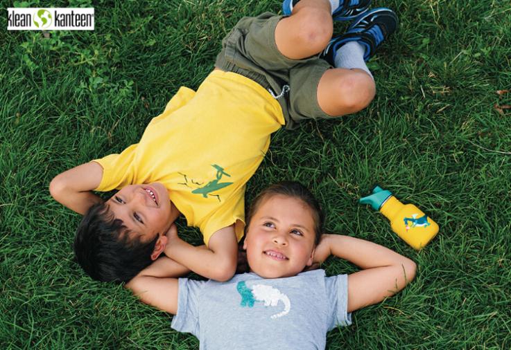 Two children lying on green grass