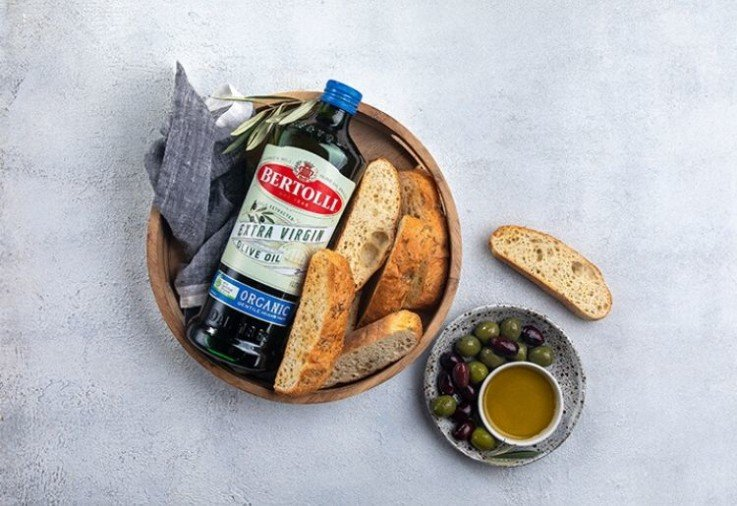 Bottle of Bertolli Olive Oil in a wooden bowl with slices of bread and olives