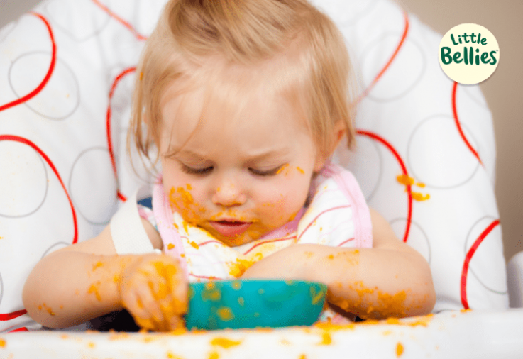 baby eating in high chair - little bellies sponsored post
